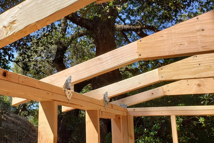 Roof trusses connected to shed frame with rafter ties.
