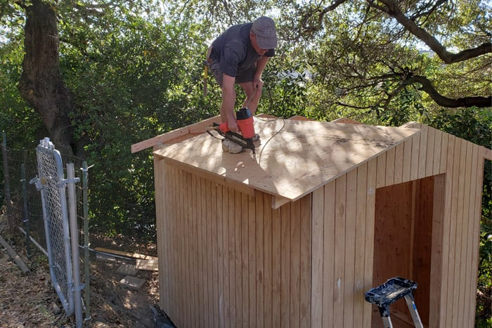 Man on roof nailing roofing to shed with nailer following 8x10 shed plans.