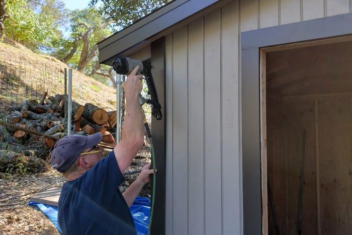 Man nails trim to corner of 8x10 storage shed.