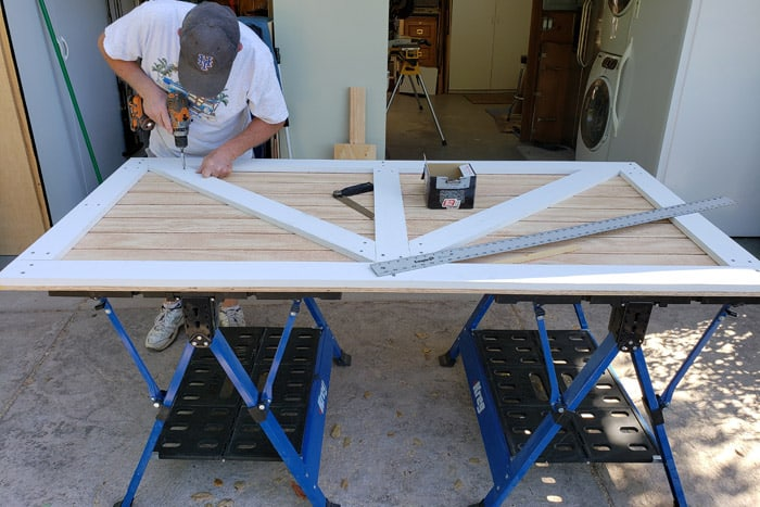 man attaching wood trim to shed door while on saw horses
