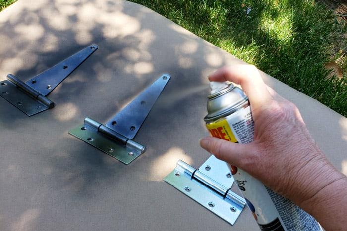 spray painting shed door hinges black.