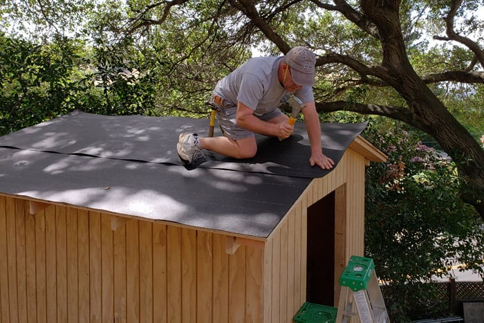 man stapling roofing felt to storage shed roof sheathing.