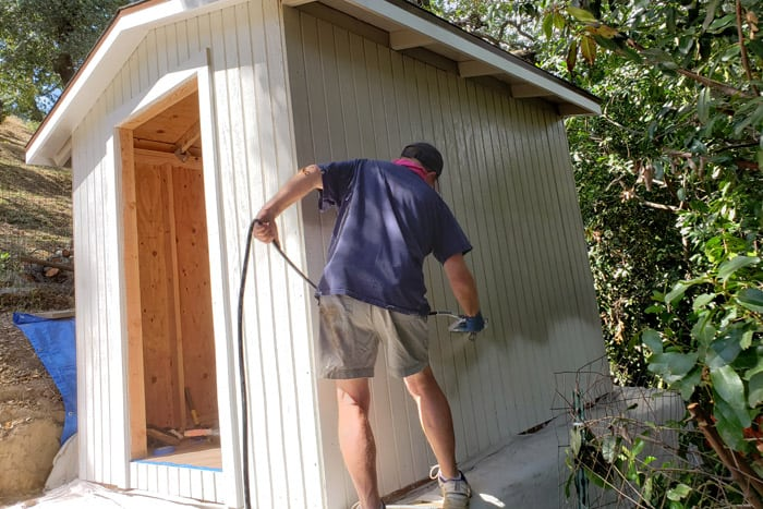 man using airless paint sprayer to paint 8x10 garden shed