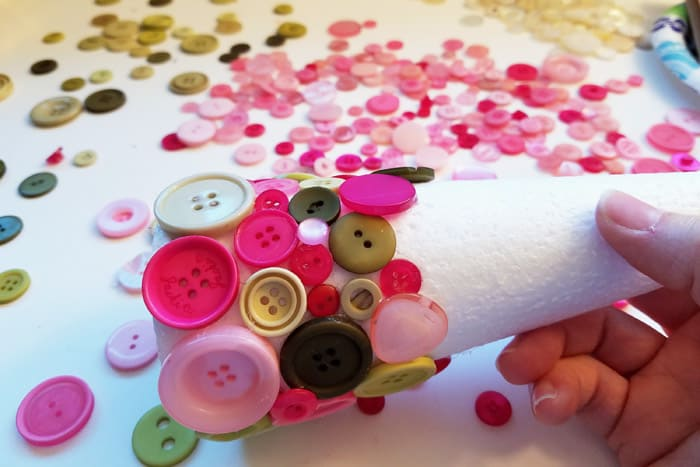 Pink and green buttons glued onto Styrofoam cone