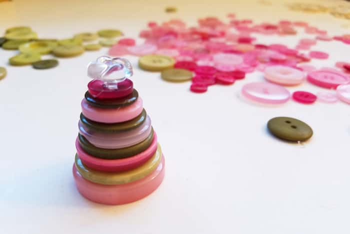 Stack of green and pink buttons with a clear topper.