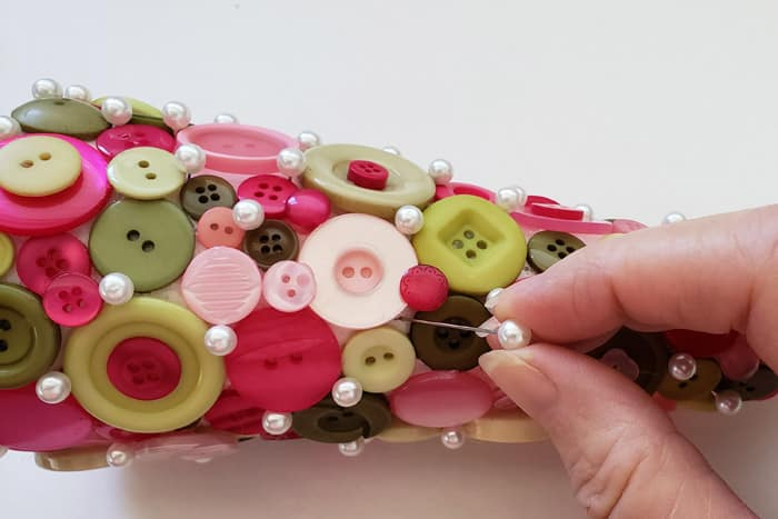 Fingers pushing floral pins into completed button Christmas Tree.
