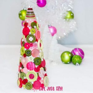 Button Christmas Tree with white metallic tree and ornaments in the background.