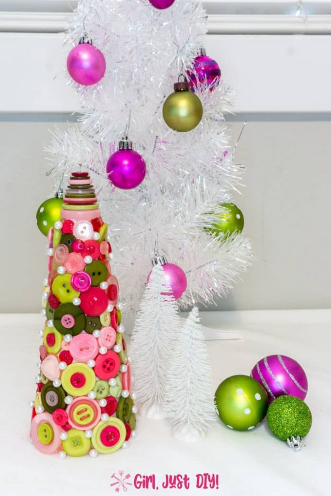 Tall picture of button Christmas tree in front of decorated table top tree.