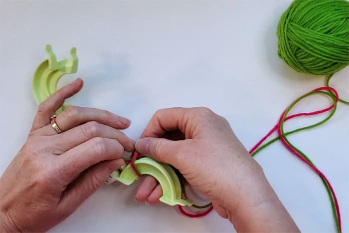 hands wrapping pink yarn around pompom maker
