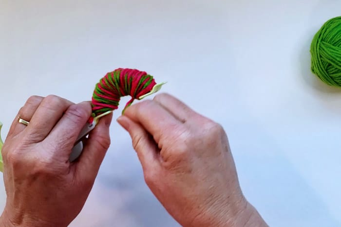 hands wrapping yarn around full pom pom maker