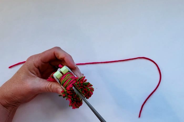 scissors cutting yarn in pompom maker
