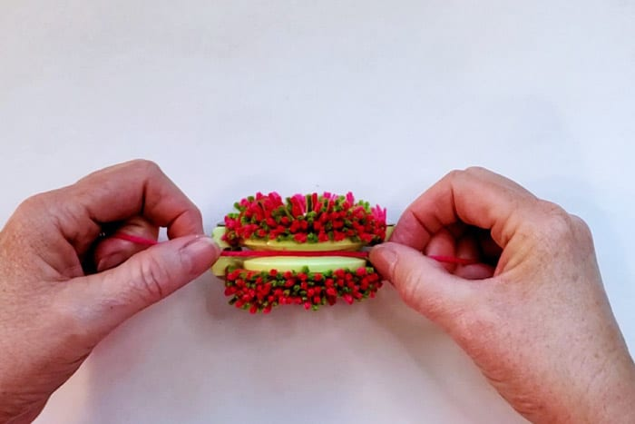 hands tying yarn around both halves of pom pom maker