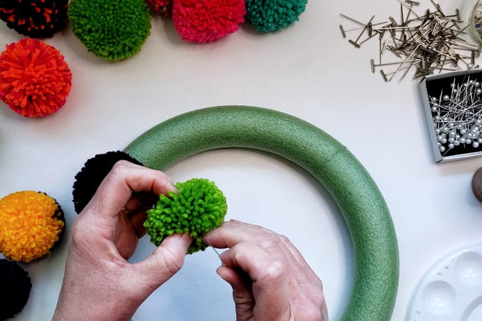 Pinning a green pompom to a wreath form.