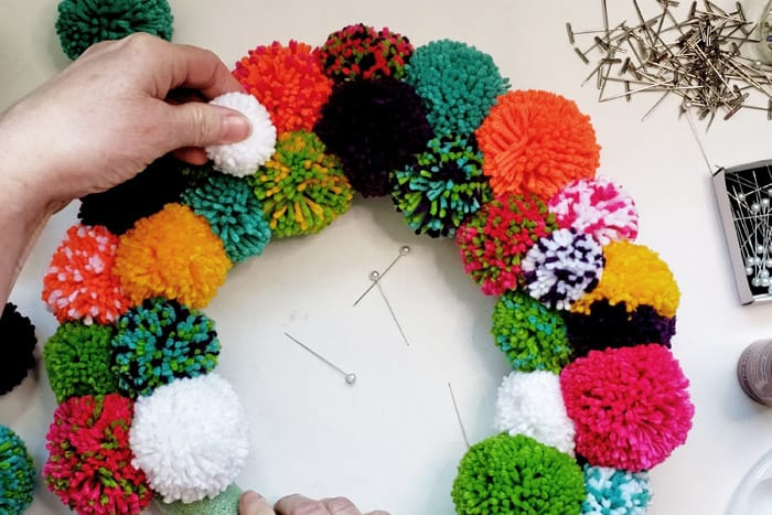 adding small white pompom to colorful diy pompom wreath