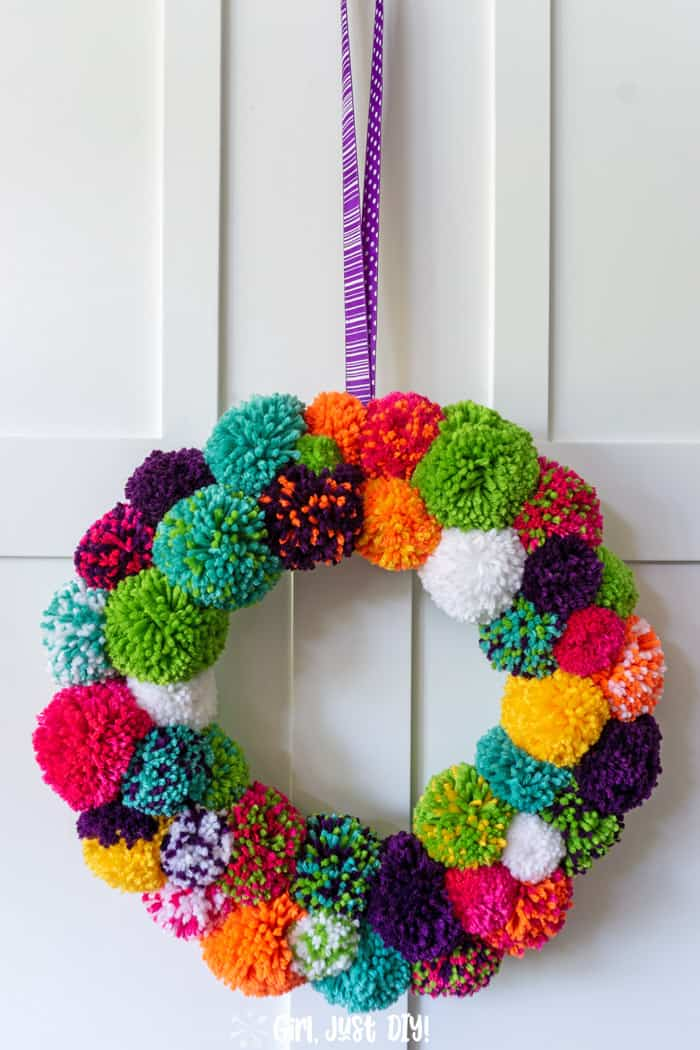 Tall view of diy pom pom wreath hanging on white door