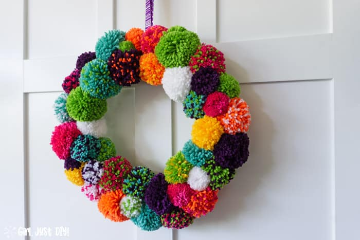 Wide picture of completed DY Pompom Wreath hanging on door.