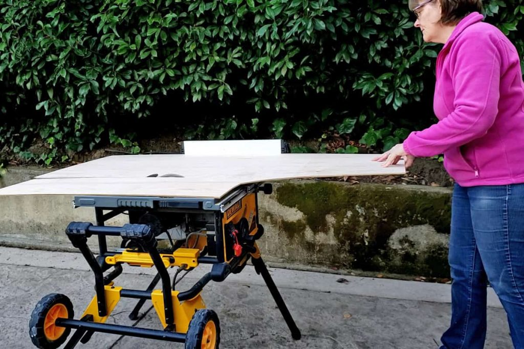 Woman cutting plywood on table saw