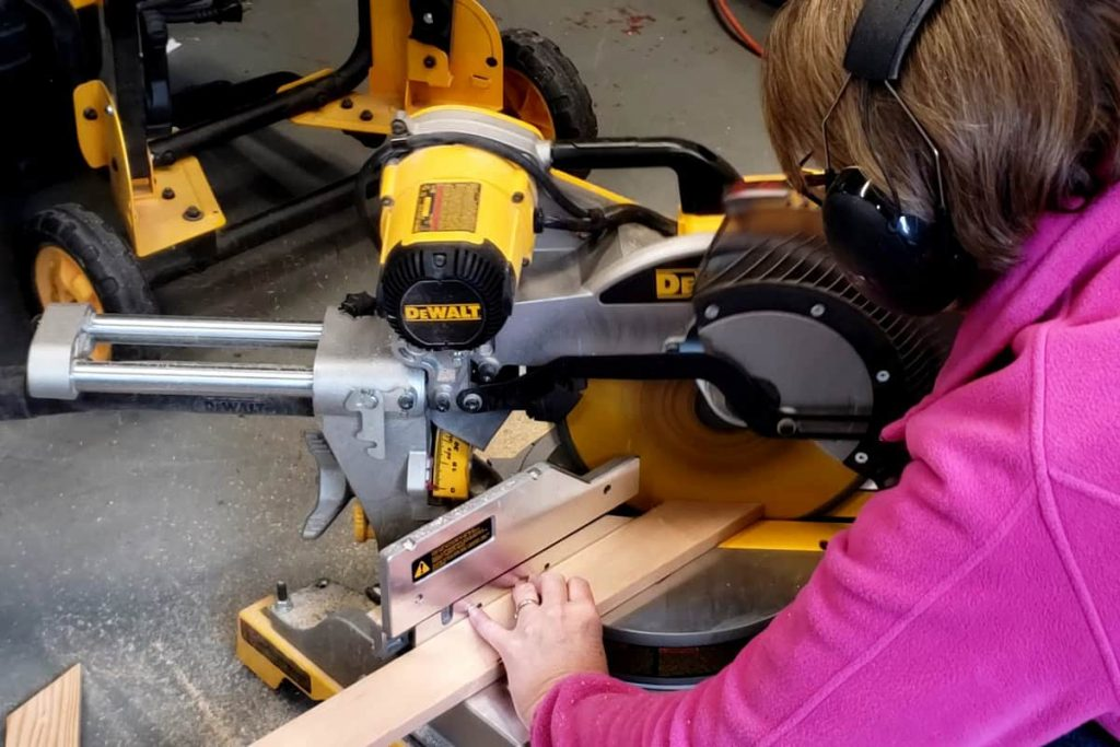 Cutting wood boards with miter saw.