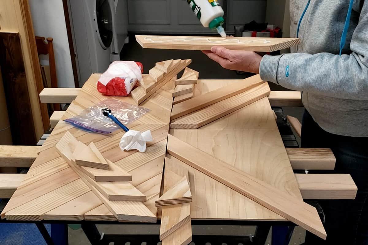 Applying wood glue to slats for chevron wall art