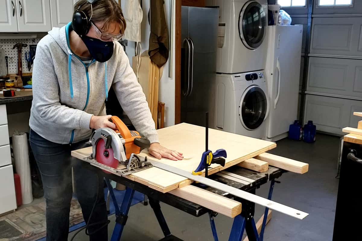woman using circular saw and cutting edge of boards